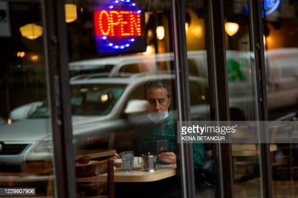 Man is having lunch inside a restaurant in New York on November 13, 2020. - Bars and restaurants in New York will shut early on November 13 under...
