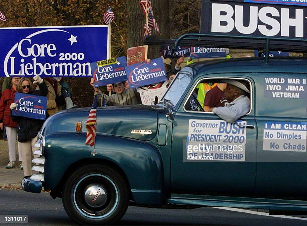 A man is heckled by supporters of Democratic presidential candidate Vice President Al Gore as he drives a vehicle decorated with signs that support...