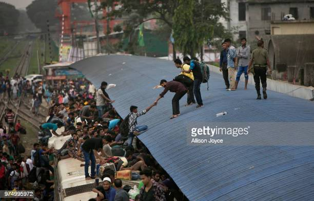 A man is helped off the roof of an overcrowded train while traveling home for Eid alFitr on June 15 2018 in Dhaka Bangladesh Muslims around the world...