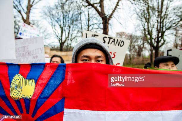 Man is hiding behind a flag, during a Rohingya solidarity rally in front of the ICJ, The Hague, on December 11th, 2019.