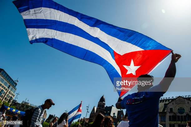 Man is holding a big Cuban flag, during the demonstration in support of Cuba organized in Amsterdam, on July 17th, 2021.
