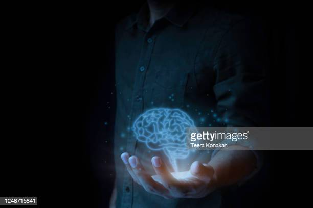 a man is holding a blue brain on a black background, the idea of finding a new business start-up idea. - launch event stock pictures, royalty-free photos & images