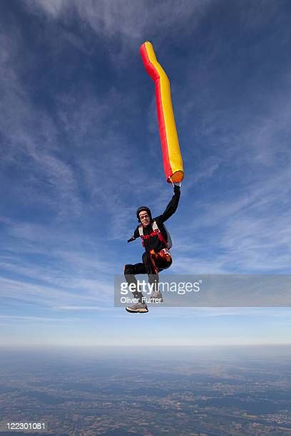 Man is holding a colourful air tube in the sky.