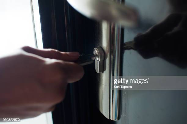 a man is holding a key to open the lock door - porta imagens e fotografias de stock
