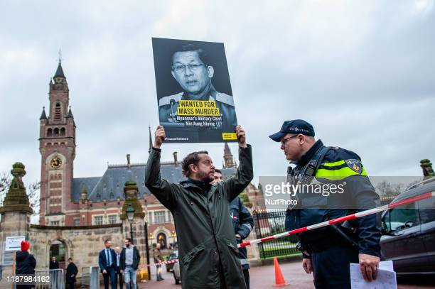 Man is holding a placard while a police officer is trying to keep away from the ICJ, in The Hague, on December 11th, 2019.