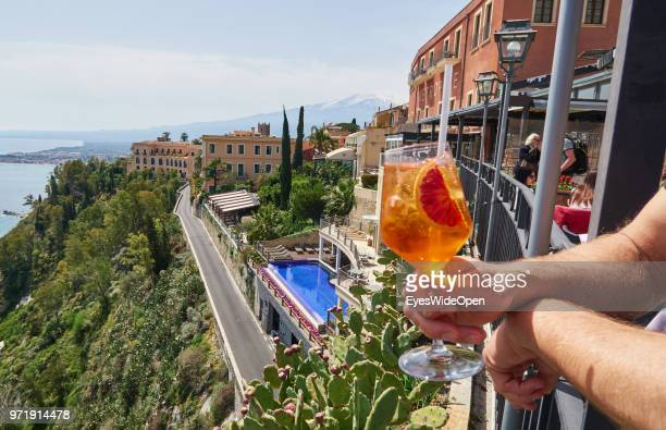A man is holding an aperitif drink Aperol Sprizz with view to Mount Etna and the ocean on April 8 2018 in Taormina Sicily Italy