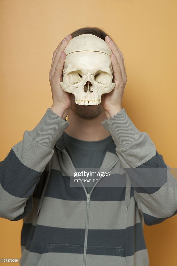 A man is holding an Death's-Head in front of the face : Photo
