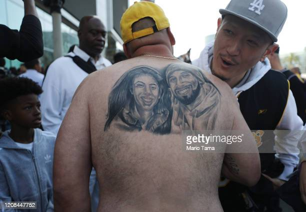 A man is hugged while he shows off a Kobe and Gianna tattoo as fans depart from the 'Celebration of Life for Kobe and Gianna Bryant' memorial service...