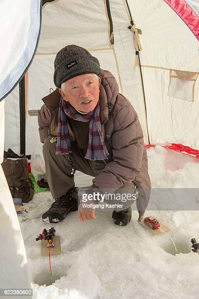A man is ice fishing in a tent on the frozen Lake Abashiriko near Abashiri a city on Hokkaido Island Japan
