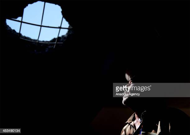 A man is in a destroyed headquarters of Islamic State formerly known as Islamic State of Iraq and the Levant militants following Peshmerga forces'...