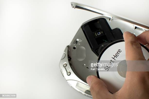A man is inserting a cd in a cd player with a start here message