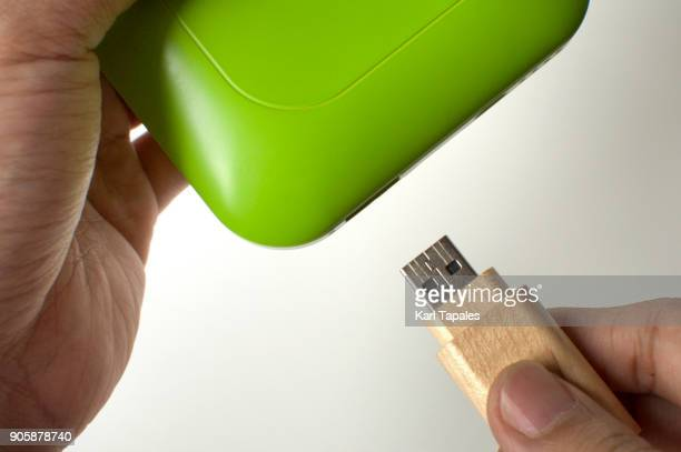 A man is inserting a flashdrive in a green powerbank