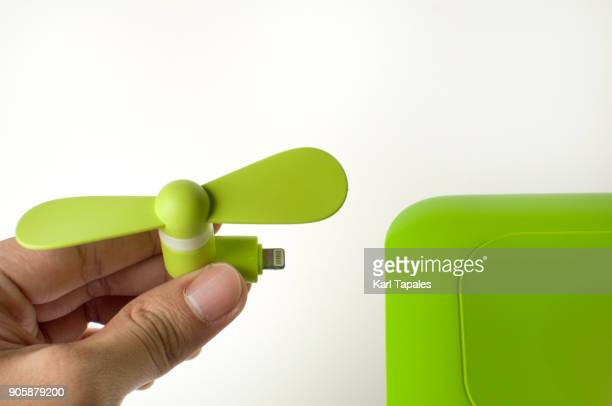 A man is inserting a green mini fan to a power bank