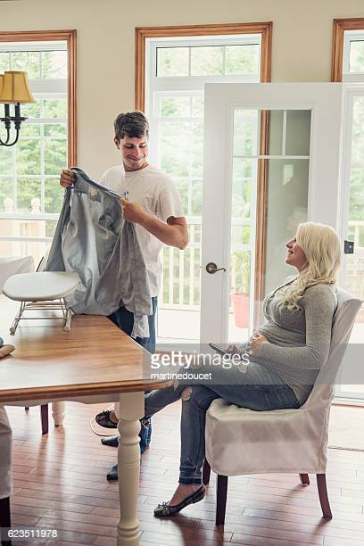 Man is ironing while pregnant woman rest with phone.