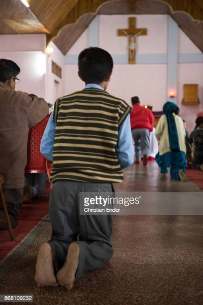 A man is kneeing and praying barefoot towards the altar inside a church in Kalimpong