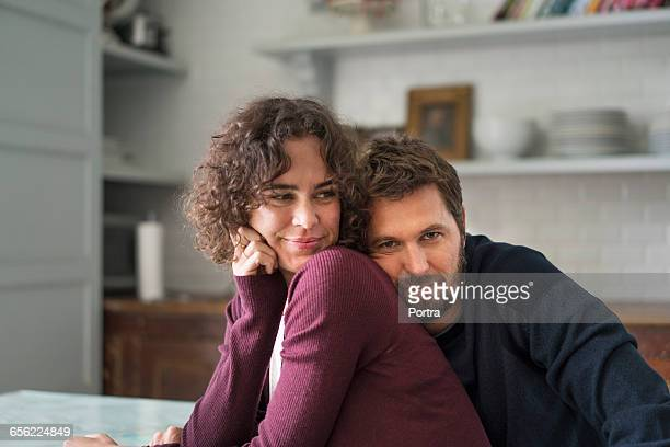 Man is leaning on female partner at home