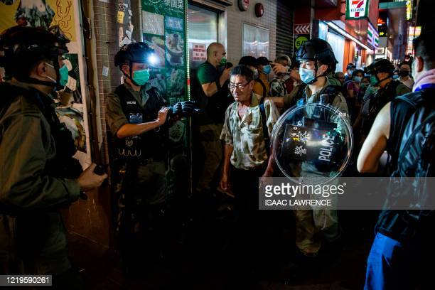 Man is led away by police as protesters gathered in the Mong Kok district of Hong Kong on June 12, 2020. - Thousands of Hong Kongers sang a protest...