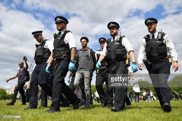 Man is led away by police officers at an anti-coronavirus lockdown demonstration in Hyde Park in London on May 16 following an easing of lockdown...