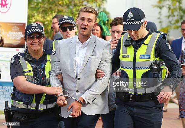 A man is led away in handcuffs by police officers following the 2015 Melbourne Cup Day at Flemington Racecourse on November 3 2015 in Melbourne...