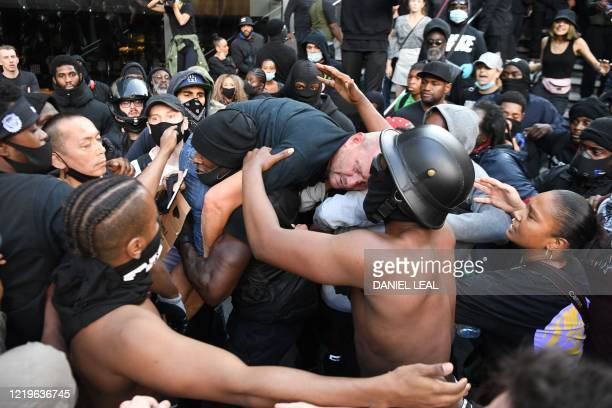 TOPSHOT A man is lifted up and taken to police lines after being beaten in clashes between protesters supporting the Black Lives Matter movement and...