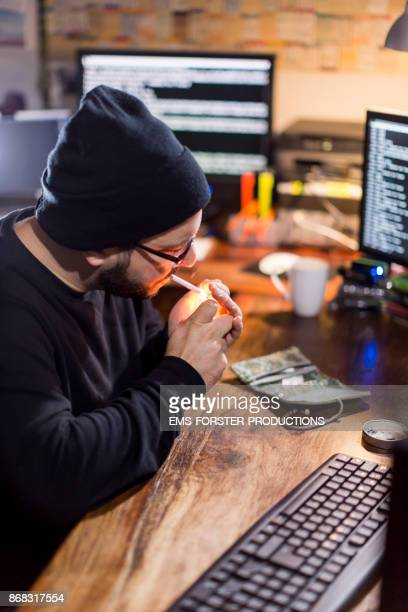 man is lighting his cigarettes in office at home