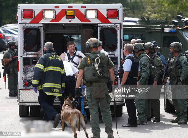 A man is loaded into an ambulance after being arrested by SWAT team members outside of a building on Cabot Street after a standoff in Medford MA on...