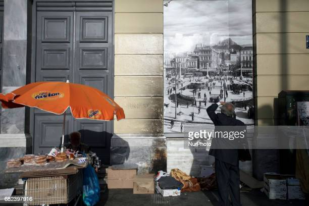 A man is looking an old image of Omonoia square next to a street vendor who sells bagels in Athens Greece May 11 2017