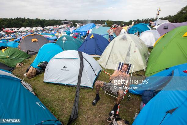 A man is looking at his smart phone among tents at the 2017 Woodstock Festival Poland on August 4 2017 in Kostrzyn Poland The threeday rock music...