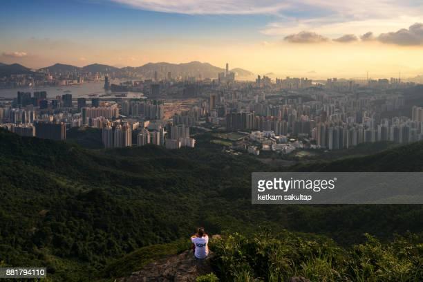 A man is looking at Hong kong city from Kowloon peak.