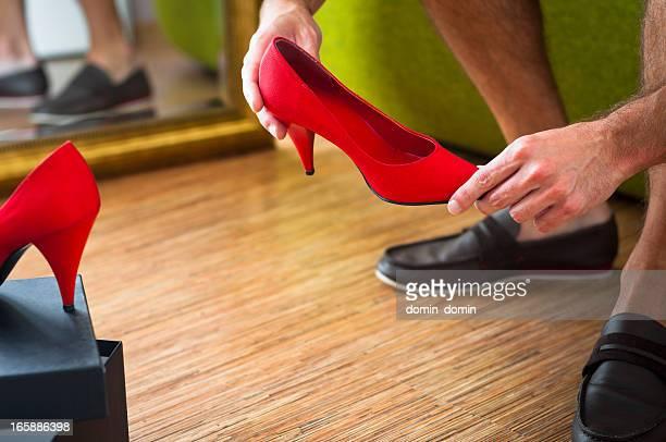 Man is looking at woman's red high-heels, wardrobe interior