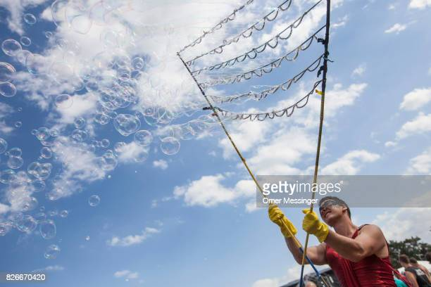 A man is making soap bubbles at the 2017 Woodstock Festival Poland on August 4 2017 in Kostrzyn Poland The threeday rock music festival now in its...