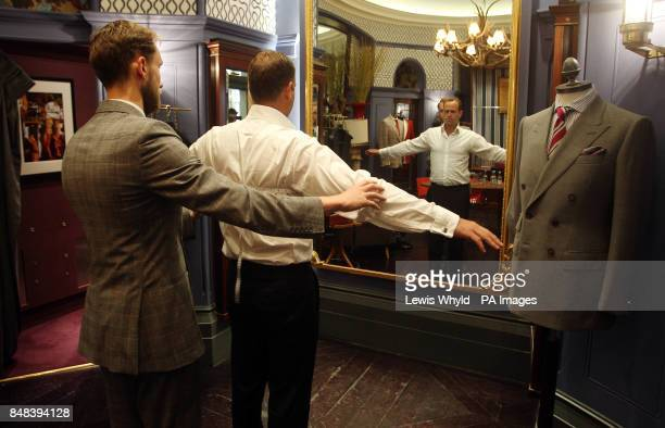 A man is measured up in the London Savile Row tailors Gieves Hawkes