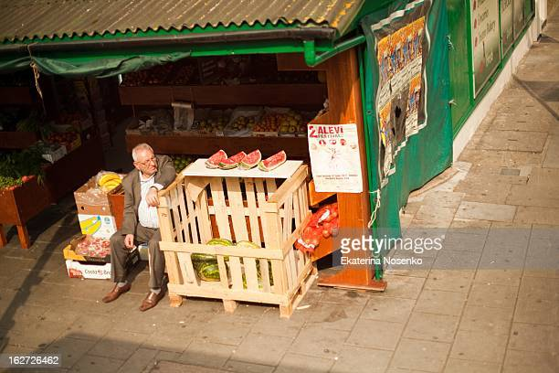 CONTENT] A man is minding a fruit store on a spring day at Dalston North London May 2012