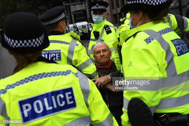 Man is moved by police officers as protestors block a junction in the City of London during an Extinction Rebellion demonstration on August 30, 2021...