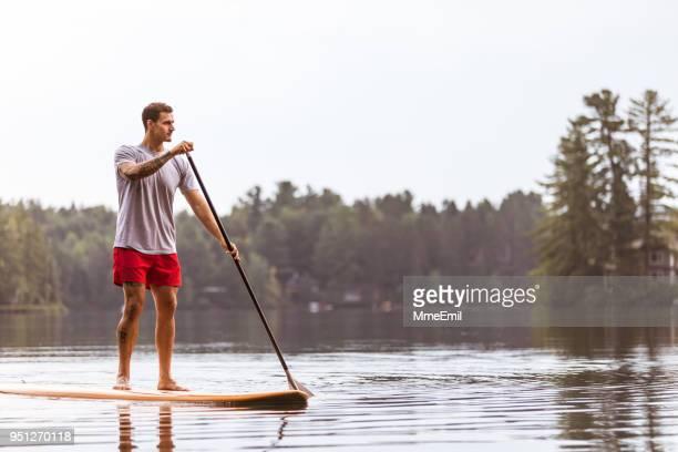 ein mann ist paddling und rudern auf einem see. sup stand up paddleboard. mauricie, quebec, kanada - seeufer stock-fotos und bilder