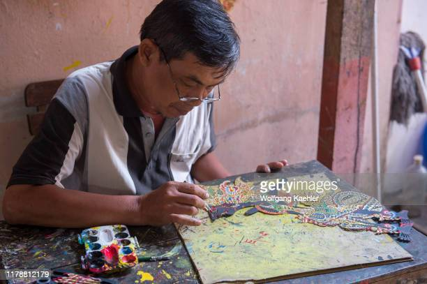 A man is painting traditional Javanese wayang kulit made out of leather in Yogyakarta Java Indonesia
