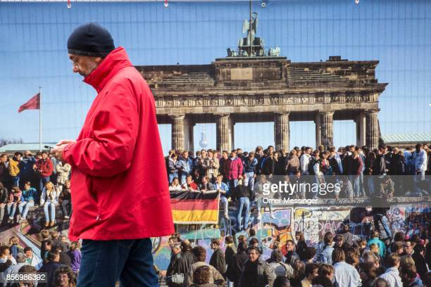 A man is passing by a poster with a seen from ttthe fall of the Berlin Wall at the entrance to an amusement area set up along 17th of June Street in...