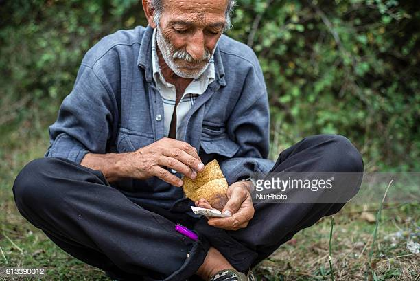 A man is picking tobacco from the pouch to roll a cigarette at Gil village Qusar district Azerbaijan on 6 October 2016 Traditional handmade tobacco...