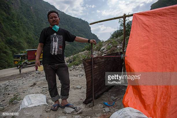 A man is pictured as he's standing near is temporary tents where 20 peoples live inside since the deadly powerful earthquake on the Araniko Road near...