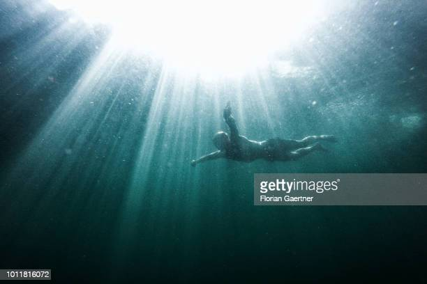 Man is pictured during diving on August 01, 2018 in Koenigshain, Germany. Farmers complain harvest losses because of the dry weather over the last...