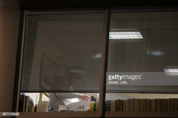 A man is pictured looking through papers inside the offices of Cambridge Analytica in central London on the evening of March 23 just hours after a...