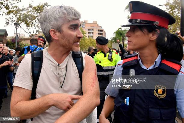 A man is pictured while speaking with an agent of the Catalan police to denounce the aggression of the Spanish police regarding the referendum...