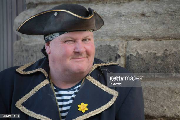 man is pirate costume welcomes visitors to whitby. - tricornered hat stock photos and pictures