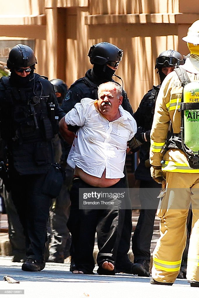 A man is placed under arrest by tactical police outside NSW Parliament House on Macquarie Street on December 20, 2013 in Sydney, Australia. The NSW Parliament House was locked down due to a security threat outside the building. A man has been apprehended after a stand off with riot police.