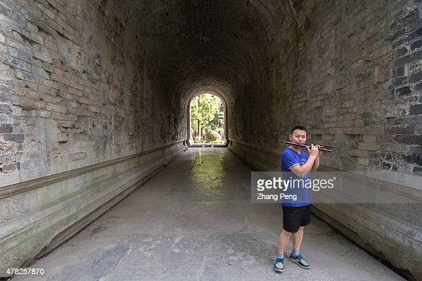 A man is playing the flute in arch pathway under the Meridian Gate Meridian Gate the only complete relic was used to be the main gate of Ming...