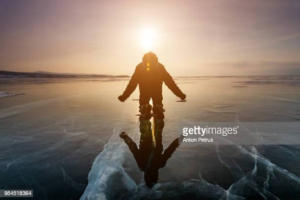 Man is practicing yoga on the ice of Lake Baikal