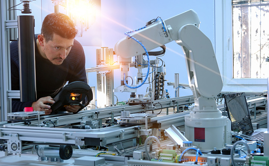 Man is programming robotic arm with control panel which is integrated on smart factory production line. industry 4.0 automation line which is equipped with sensors and robotic arm 1187225170