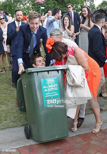 A man is pushed into a rubbish bin following 2016 Melbourne Cup Day at Flemington Racecourse on November 1 2016 in Melbourne Australia