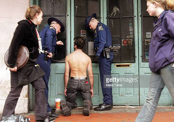 A man is questioned by police officers on Bourbon Street during Mardi Gras festivites February 6 2005 in New Orleans Louisiana Festivities will...