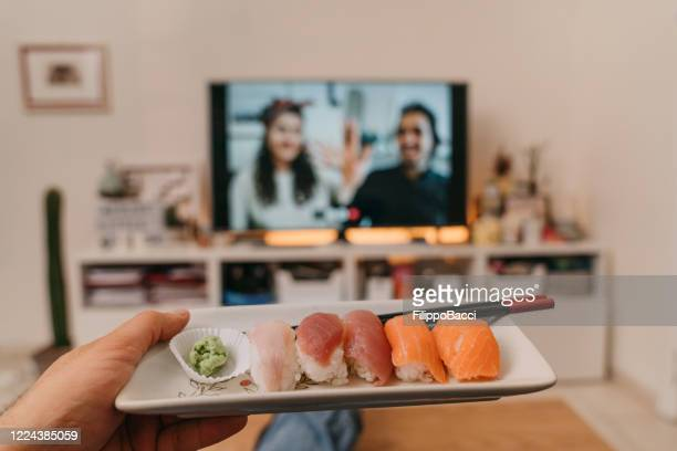 man is ready to eat sushi in front of tv - video call with friends on the tv screen - wasabi stock pictures, royalty-free photos & images